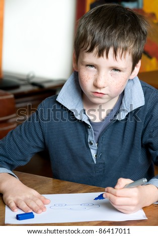 young boy draws and thinking