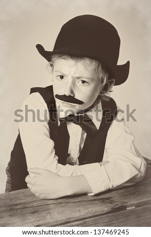 Young boy dressed as a old West bartender with a scowl