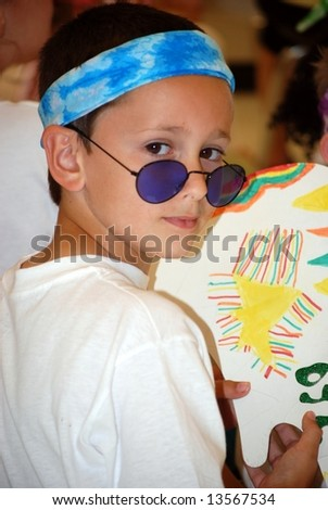 Young boy dressed as a youth of the 60's. - stock photo