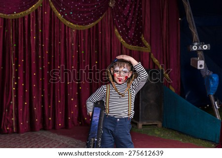 Young Boy Dressed as Clown Wearing Combat Helmet and Striped Shirt Holding Large Gun on Stage with Red Curtain - stock photo