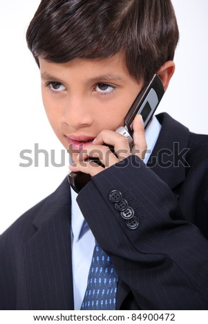 Young boy dressed in a business suit with a mobile phone - stock photo