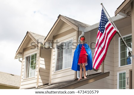 Young boy dressed in superhero costume on the roof of his house