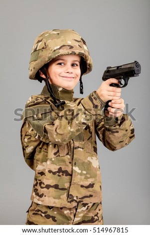 Young boy dressed like a soldier with a gun isolated on gray background