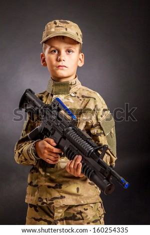 Young boy dressed like a soldier with rifle isolated on black background