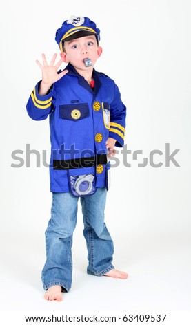 Young boy dressed up as a police officer who is blowing a whistle on white background. - stock photo