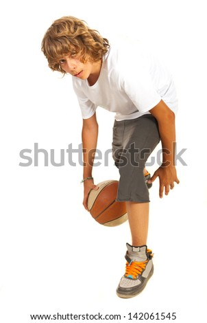 Young boy dribbling basketball isolated on white background - stock photo