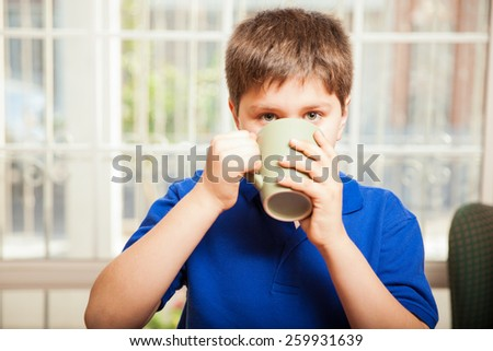 Young boy drinking some coffee from a mug and making eye contact - stock photo