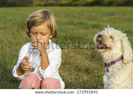 Young boy drinking water whilst playing outdoors on the grass with his cute dog - stock photo