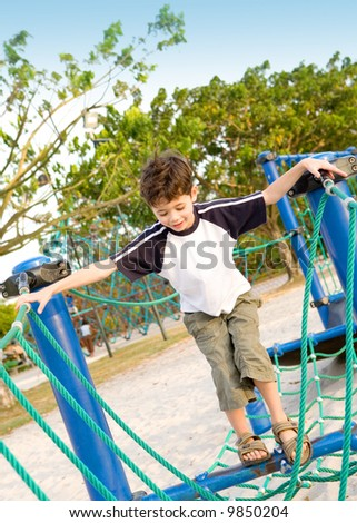 Young boy eager to cross the playground rope activity challenge. - stock photo