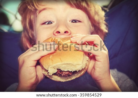 young boy eating a hamburger outdoors, vintage instagram effect. - stock photo