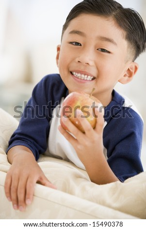 Young boy eating apple in living room smiling - stock photo