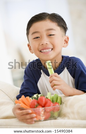 Young boy eating bowl of vegetables in living room smiling - stock photo