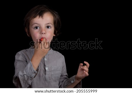 Young boy eating candy. Black background. - stock photo