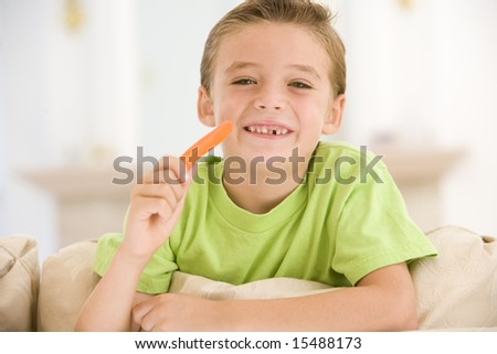 Young boy eating carrot stick in living room smiling - stock photo