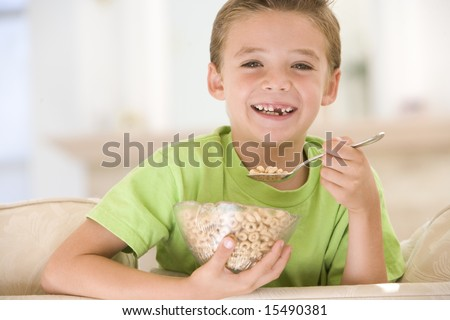 Young boy eating cereal in living room smiling - stock photo