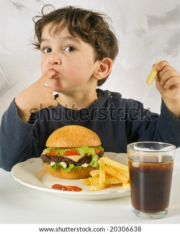 young boy eating cheeseburger with french fries and coke