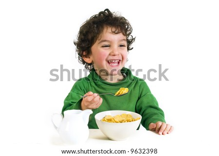 young boy eating cornflakes isolated on white - stock photo