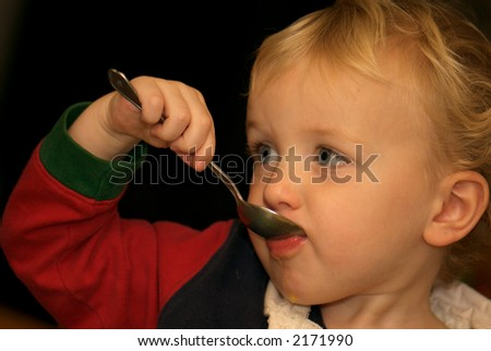 Young boy eating dinner - stock photo