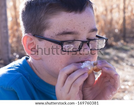 Young boy eating funnel cake in corn field. - stock photo
