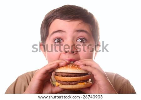 Young boy eating hamburger - stock photo