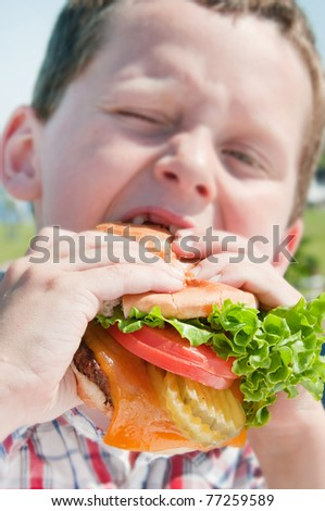 Young boy eating huge burger at cookcout - stock photo