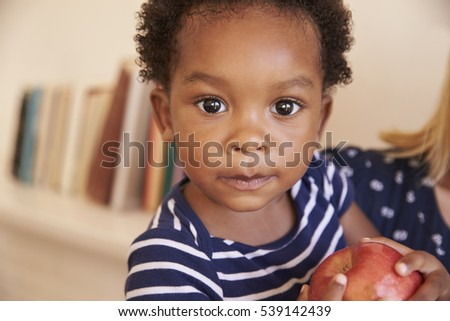Young Boy Eating Red Apple At Home