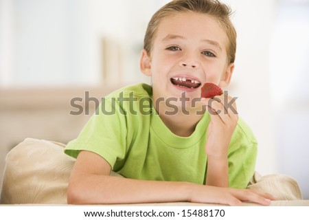 Young boy eating strawberries in living room smiling - stock photo