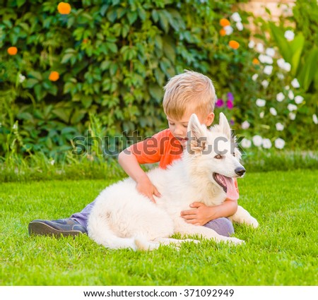 Young boy embracing White Swiss Shepherd`s puppy on green grass. - stock photo