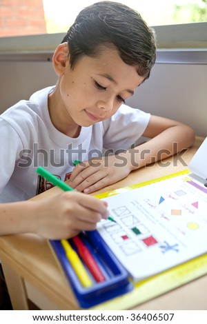 Young boy engross doing his math coloring homework