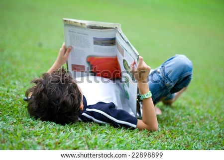 Young boy engross in his reading book in an outdoor park - stock photo