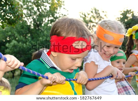 Young boy enjoying a tug of war at a party peering over the rope with a look of amazement on his face watched by his laughing young sister