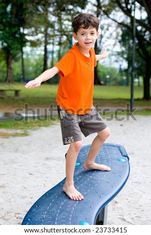 Young boy enjoying balancing beam in outdoor park - stock photo