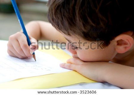 Young boy enjoying his handwriting homework, doing it outdoors in summer.