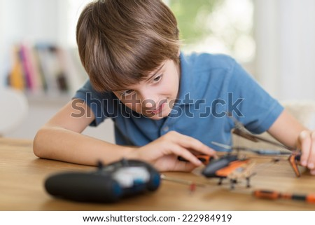 Young boy enjoying his hobby sitting at a table at home contentedly playing with a smile on his face