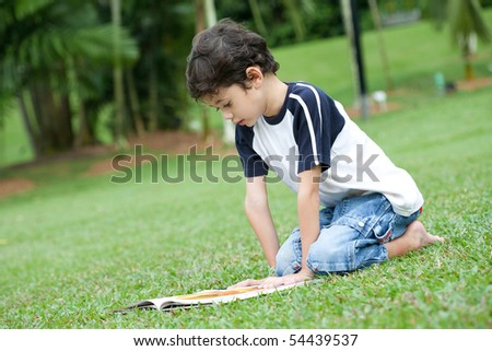 Young boy enjoying his reading book in outdoor park - stock photo