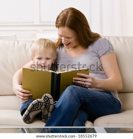 Young boy enjoying listening to mother head him a story in livingroom