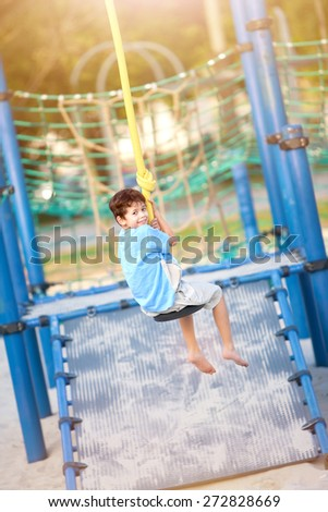 Young boy enjoying on balancing activity at the outdoor park in evening sun. - stock photo