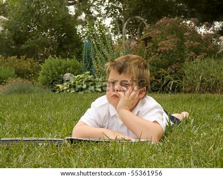 Young boy enjoying summer day while laying outside ont he grass and reading book - stock photo