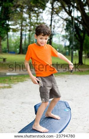Young boy enjoying the balancing beam in outdoor park - stock photo