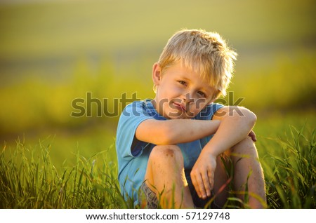 young boy enjoys his time outside in the field - stock photo