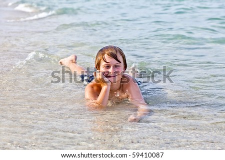 young boy enjoys lying at the beach in the surf