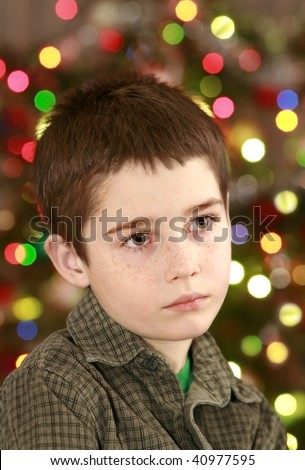 young boy face on the christmas tree with colorful lights background, expecting of gifts