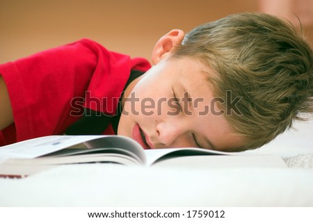 Young boy fell asleep after hard studying - stock photo