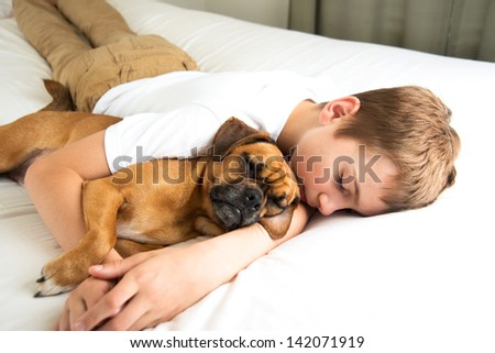 Young Boy Fell asleep Hugging his Dog - stock photo