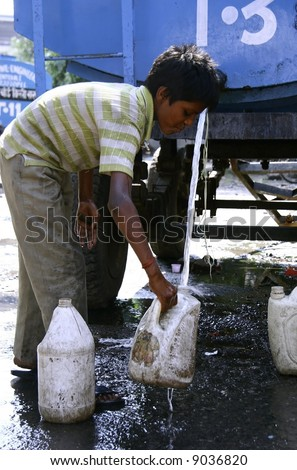 young boy filling up water in cans, delhi, india - stock photo