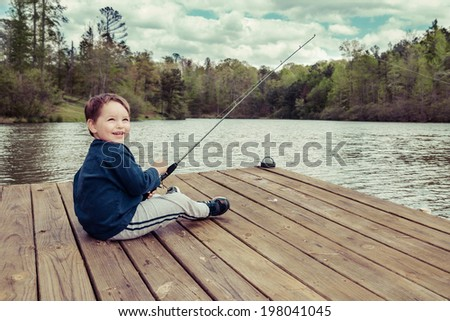 Young boy fishing from dock on sunny spring day in image with vintage filter - stock photo