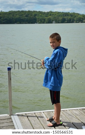 young boy fishing off  a dock - stock photo
