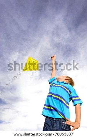 Young boy flies a yellow kite on a windy summer day - stock photo