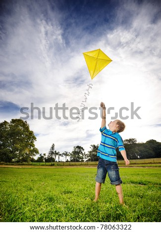 Young boy flies his kite in an open field. a pictorial analogy for aspirations and aiming high - stock photo