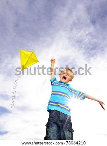 Young boy flies his yellow kite on a sunny day; a pictorial analogy for ambition - stock photo